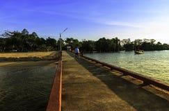 Bemannen Sie Reitfahrrad auf der Brücke mit schönem Sonnenuntergang Stockfotos