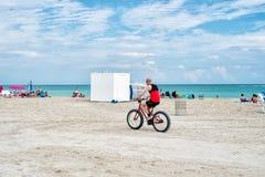 Bemannen Sie Reitfahrrad auf sandigem Strand entlang blauer Seeküste Lizenzfreie Stockfotografie