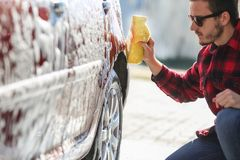 Bemannen Sie ` s Auto der Arbeitskraft waschende Leichtmetallräder auf einer Waschanlage stockfotos