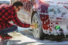 Bemannen Sie ` s Auto der Arbeitskraft waschende Leichtmetallräder auf einer Waschanlage stockbilder