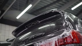Bemannen Sie ` s Auto der Arbeitskraft waschende Leichtmetallr?der auf einer Waschanlage Waschanlage waschen das Auto an der Wasc lizenzfreie stockfotografie
