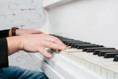 Bemannen Sie ` s Hände auf Tastatur des weißen Klaviers lizenzfreie stockfotos
