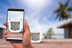 Bemannen Sie ` s Hände, die den Smartphone halten, der QR-Code auf Kaffeetasse neben dem Strand scannt Lizenzfreies Stockbild