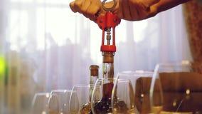 Bemannen Sie ` s Hände, welche die Flasche des Weins auf gedienter Tabelle in der Zeitlupe öffnen 1920x1080 stock footage