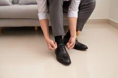 Bemannen Sie ` s H?nde, die Spitze seiner neuen Schuhe binden Mannbein und -h?nde, die Schn?rsenkel binden stockfoto
