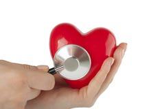 Bemannen Sie ` s Hand, die ein rotes Herz und ein Stethoskop hält Lizenzfreie Stockfotografie