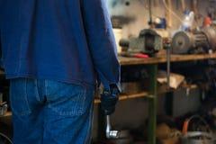 Bemannen Sie ` s Hand, die einen Sockelmetallschlüssel mit Ratsche im Kaimanfisch hält Lizenzfreie Stockfotos