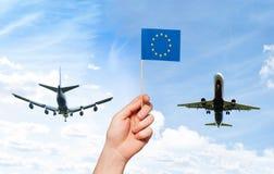 Bemannen Sie ` s Hand, die Flagge der Europäischen Gemeinschaft mit Pfosten hält Stockbild