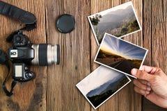 Bemannen Sie ` s Hand, die Foto mit alter Schmutzkamera und Fotos auf hölzernem Hintergrund des Weinleseschmutzes hält Lizenzfreie Stockbilder