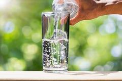Bemannen Sie ` s Hand, die Trinkwasserflaschenwasser hält und Wasser in Glas auf hölzerner Tischplatte auf unscharfem grünem boke Stockfoto