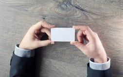 Bemannen Sie ` s Hand, die Visitenkarte - die Nahaufnahme zeigt, die auf dunklem hölzernem Hintergrund geschossen wird Stockfotografie