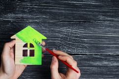 Bemannen Sie ` s Handfarben das Holzhaus in der grünen Bürste Reparatur und Erneuerung des Hauses, umweltfreundliches Haus Energi stockfotografie