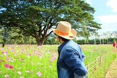 Bemannen Sie ` s hinteren tragenden Strohhut beim Betrachten des Blumengartens stockfotos