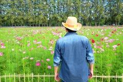 Bemannen Sie ` s hinteren tragenden Strohhut beim Betrachten des Blumengartens stockbild