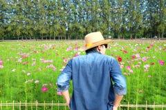 Bemannen Sie ` s hinteren tragenden Strohhut beim Betrachten des Blumengartens lizenzfreies stockbild