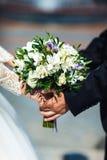 Bemannen Sie ` s und weibliche Hand hält einen Hochzeitsblumenstrauß stockfoto