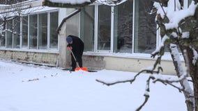 Bemannen Sie sauberes cnow mit Schaufel nahe Hausmauer mit großem Fenster 4K stock footage