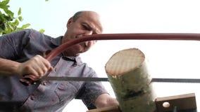 Bemannen Sie Sawingholz für Lagerfeuer im Landhaus Nahaufnahme sah und Holzfällerausschnittbäume draußen stock video footage