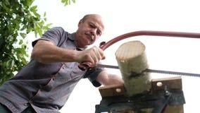 Bemannen Sie Sawingholz für Lagerfeuer im Landhaus Nahaufnahme sah und Holzfällerausschnittbäume draußen stock footage