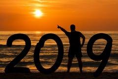 Bemannen Sie Schattenbildjahr 2019 bei Sonnenaufgang in Meer Stockfoto