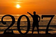 Bemannen Sie Schattenbildjahr 2017 bei Sonnenaufgang in Meer Stockfoto