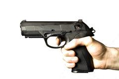 Bemannen Sie Schießen .45 Kaliber Pistole, die auf Weiß getrennt wird Stockfotos