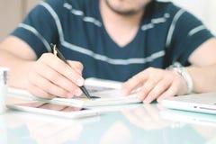 Bemannen Sie Schreiben auf der Zeitschrift mit einem Stift lizenzfreie stockbilder