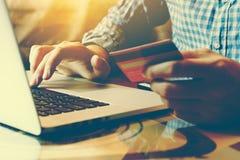 Bemannen Sie Schreibenlaptoptastatur und Haltenkreditkarte mit on-line-s Lizenzfreie Stockfotos