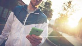 Bemannen Sie Schreibenmitteilung an seinem Handy und das Gehen auf die Straße bei Sonnenuntergang Stockbilder