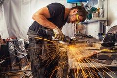 Bemannen Sie Schweißung in Prozesse ein Metall mit einem Winkelschleifer stockfoto