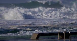 Bemannen Sie Schwimmen mit den großen Wellen, die Ozeanbäder schlagen stock video