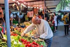 Bemannen Sie seects Stangenbohnen an einem Straßenmarkt in Paris Stockfotos