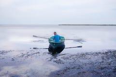 Bemannen Sie Segeln auf einem kleinen Ruderboot entlang der Seeküste Stockfoto