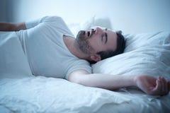 Bemannen Sie in seinem Bett laut schlafen und schnarchen lizenzfreies stockfoto