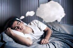 Bemannen Sie in seinem Bett mit einer Wolke bequem träumen lizenzfreies stockbild