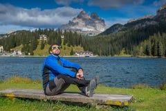 Bemannen Sie Sitzplätze auf Bank nahe Lago di Misurina im sout Tirol, italien Dolomit, Tre cime di Lavaredo Stockfotos
