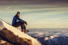 bemannen Sie Sitzplätze auf Berg, bewundern Winterlandschaft des männlichen Wanderers auf einer Bergspitze allein mit Eisaxt Stockfoto