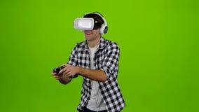 Bemannen Sie Spiele auf gamepad mit Kopfhörern und vr Gläsern studio stock video footage