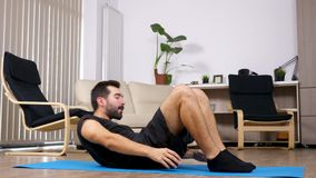 Bemannen Sie Sport zu Hause tun, er macht Übungen für die ABS stock video