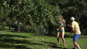 Bemannen Sie Spraywasserschlauch auf Frau im Bikini Paare im Sommer 4K stock video footage