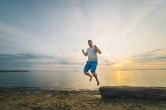 Bemannen Sie springen auf den Strand mit Sonnenaufgang auf Hintergrund Stockfoto
