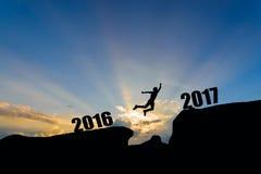 Bemannen Sie springen zwischen 2016 und 2017 Jahre auf Sonnenunterganghintergrund Stockfoto