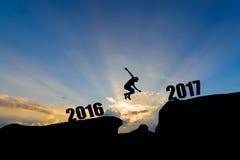 Bemannen Sie springen zwischen 2016 und 2017 Jahre auf Sonnenunterganghintergrund Stockbild
