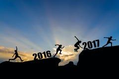 Bemannen Sie springen zwischen 2016 und 2017 Jahre auf Sonnenunterganghintergrund Stockbilder