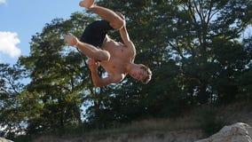 Bemannen Sie springendes sideflip auf dem Strand bei Sonnenuntergang Freerunner, das akrobatische Bremsung springt stock video footage