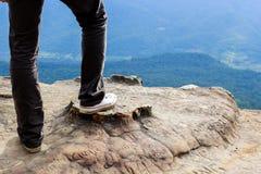 Bemannen Sie Stand auf dem Bergspitzefelsen und übersteigen Sie den Bergblick stockfoto