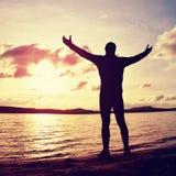 Bemannen Sie Stand nahe dem Strand, der Sonnenuntergang, ruhigen Wasserspiegel betrachtet Stockfotos