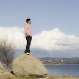 Bemannen Sie Stellung auf dem Felsen, der Abstand untersucht stockfotografie