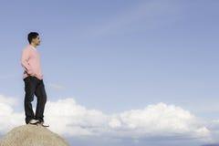 Bemannen Sie Stellung auf dem Felsen, der Abstand untersucht lizenzfreie stockbilder