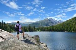 Bemannen Sie Stellung auf eine Oberseite des Berges, der Bergblick genießt Stockbild